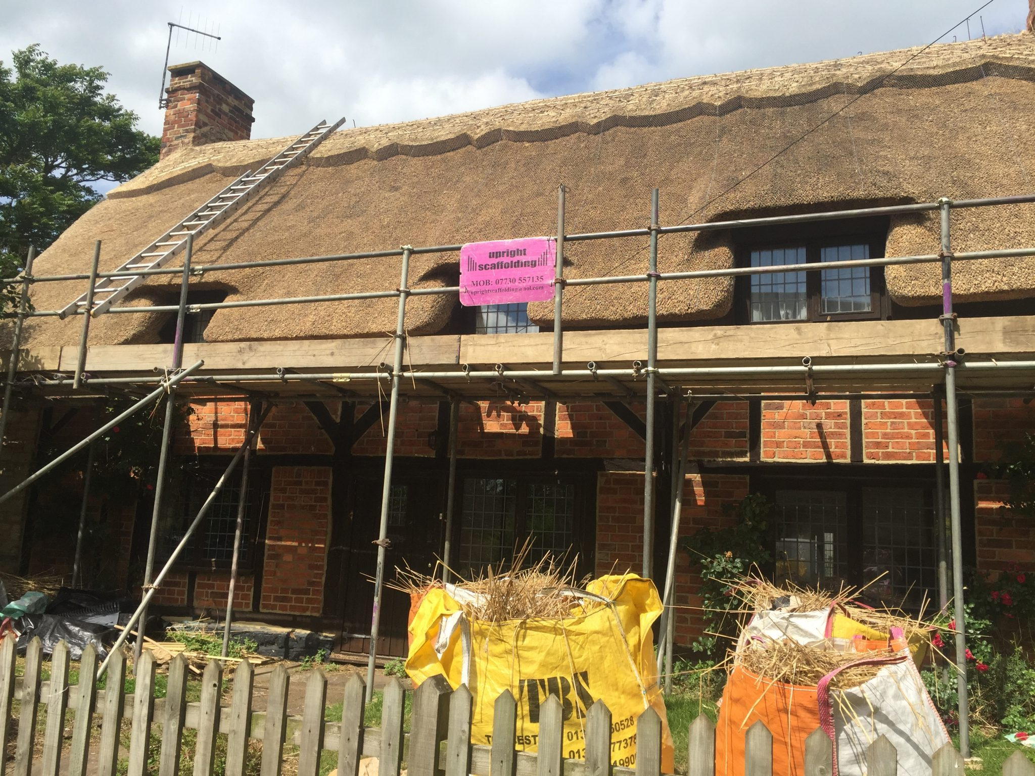 water reed thatched roof on brick house with scaffolding